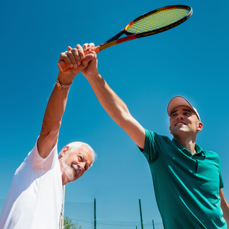 70s tennis: Tennis instructor with senior man on tennis class Stock Photo