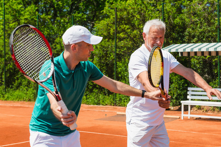 70s tennis: Tennis class - instructor working with senior adult