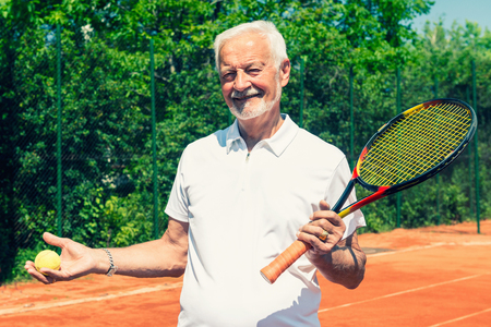 70s tennis: Senior tennis player with ball and racket