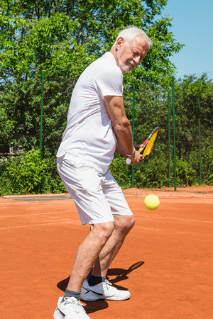 70s tennis: Senior man playing tennis