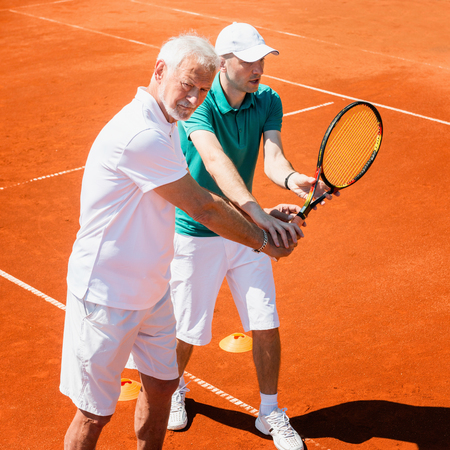 70s tennis: Senior man practicing with tennis instructor