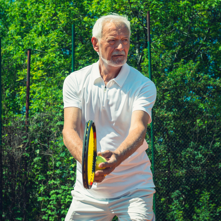 70s tennis: Senior tennis player on serve Stock Photo