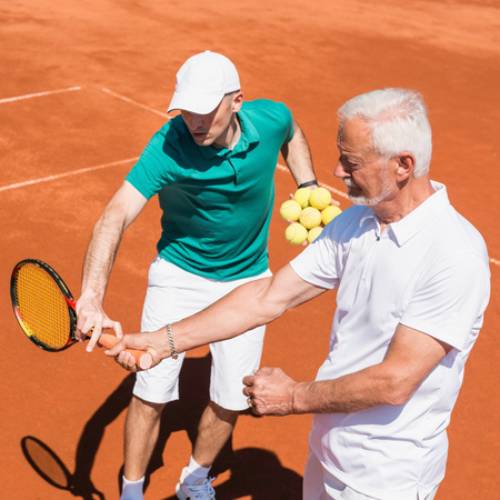 70s tennis: Senior man having tennis lesson with instructor Stock Photo