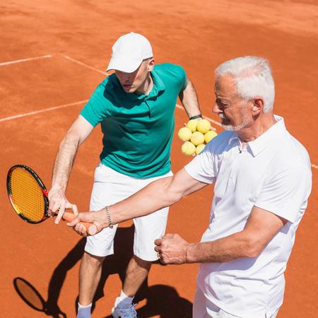 70s tennis: Senior man having tennis lesson with instructor Stock Photo