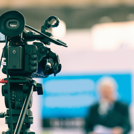 commercial event: Television news. Camera in focus, TV announcer blurred