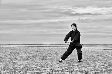 qigong: Woman doing Qi Gong in desert, high contrast