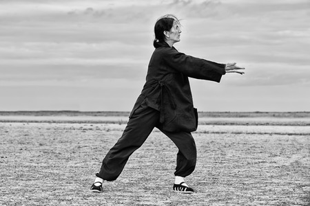 combative sport: Woman practicing Qi Gong, gathering energy