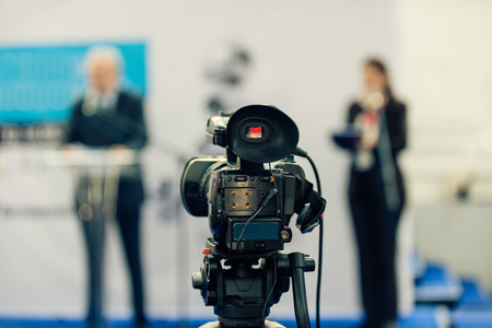 commercial event: Public relations - PR manager talking to media at press conference. Camera in focus