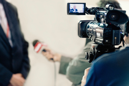 spokesman: TV Media Interview - Journalist interviewing businessman or politician, camera recording Stock Photo