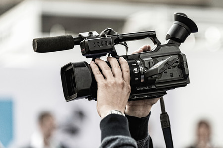 commercial event: Cameraman holding tv camera high above