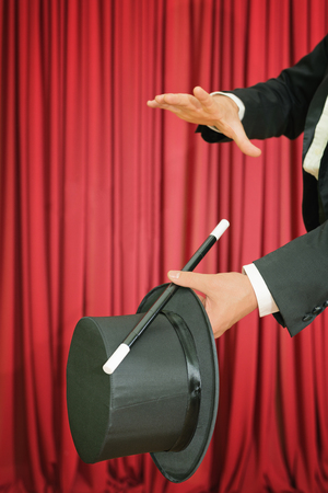 magic trick: Magic trick with magic wand and top hat on stage. Stock Photo