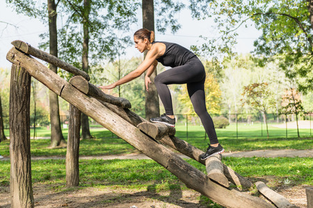recreational climbing: Female athlete crossing wooden barriers on fitness trail