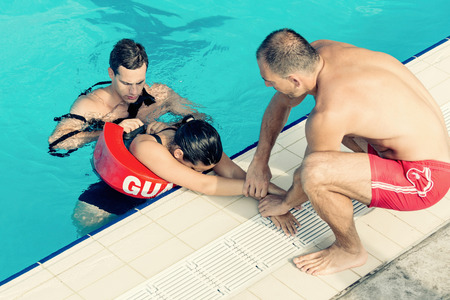 flotation: Lifeguards in training - Rescuing female victim from public swimming pool Stock Photo