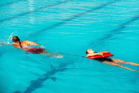 safety buoy: Lifeguard training - lifeguard pulling victim to safety, using floating rescue buoy