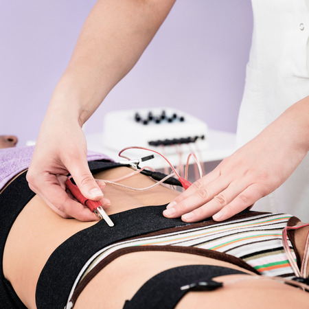 stimulation: Placing electrodes for electro stimulation of muscles in waist area