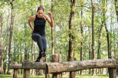 Female athlete running across wooden hurdles in park