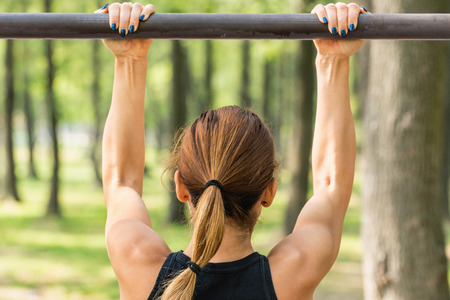 Back view of female athlete doing chin-ups