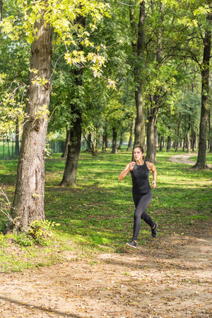 strenght: Female athlete jogging outdoors Stock Photo