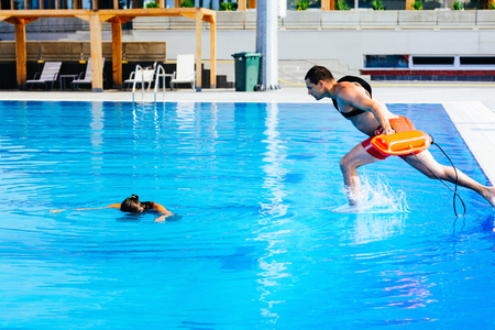 Lifeguard rescue training - young man jumping into a swimming pool to rescue drowning victim Stock Photo