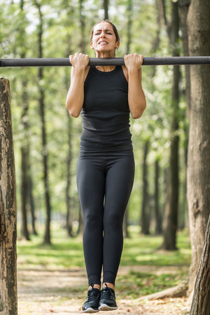 outdoor training: Female athlete doing chin-ups in park
