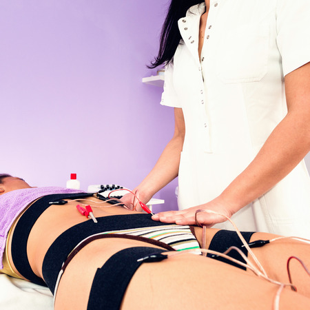 stimulation: Muscle electro stimulation in beauty salon Stock Photo