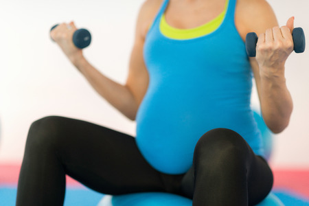 prenatal: Prenatal exercising - Pregnant woman doing simple execise with dumbbels, sitting on fitness ball Stock Photo