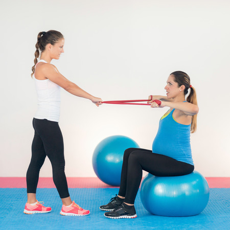 two persons only: Third trimester pregnant woman doing simple resistance band exercises with fitness instructor