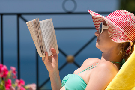 longue: Woman reading a book on vacation in longue chair