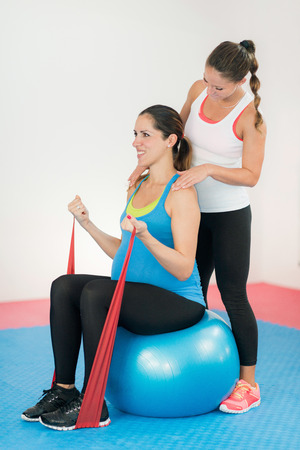 trimester: Third trimester pregnant woman exercising. Soft, easy training with fitness ball and resistance band. Fitness instructor giving support. Stock Photo