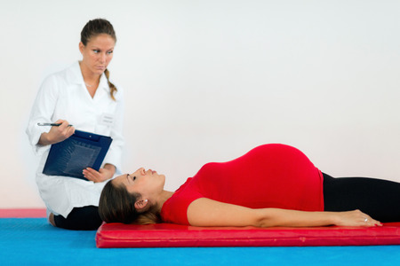 midwife: Breathing execise in pregnancy - Pregnant woman with midwife or maternity consultant Stock Photo