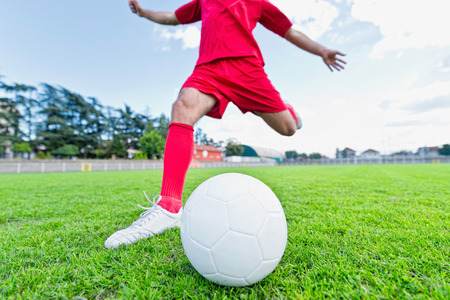 uniform green shoe: Soccer player about to kick soccer ball on stadium Stock Photo