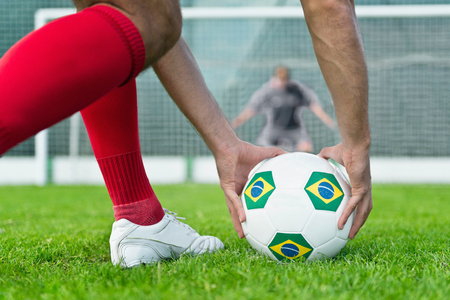uniform green shoe: Soccer player placing Brazilian ball on penalty kick spot Stock Photo