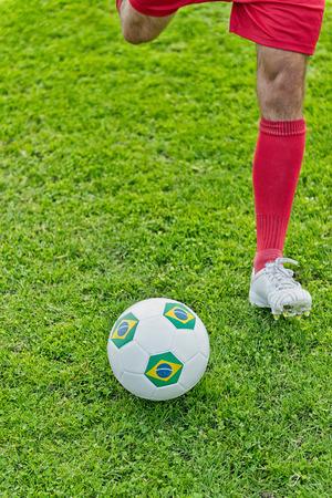 striker: Soccer striker kicking the ball with Brazilian flag markings