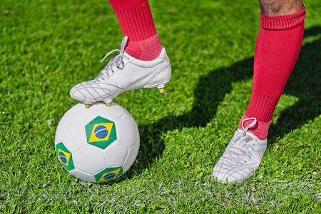 uniform green shoe: Football player with foot on ball with Brazils flag