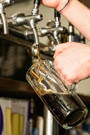 draught: Pouring draught stout beer in pub Stock Photo