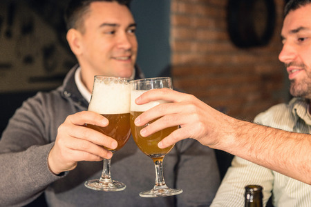 drinks after work: Friends toasting with beer in a pub Stock Photo