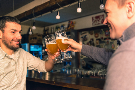 drinks after work: Friends in bar having good time, toasting with beer Stock Photo