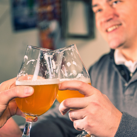 drinks after work: Friends toasting with wheat beer in pub. Focus on glasses, toned image.