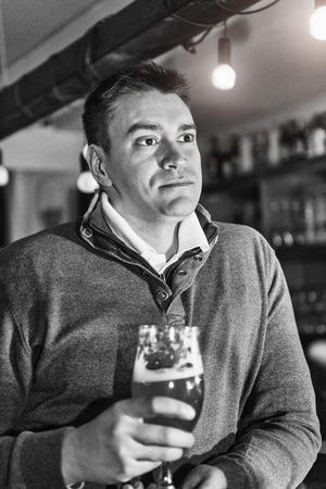 drinks after work: Portrait of a serious mid adult man having beer in pub