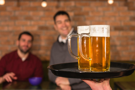 drinks after work: Waiter bringing beer for friends