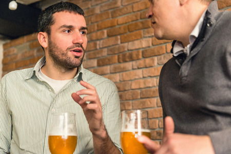 beer after work: Friends chatting over beer in bar