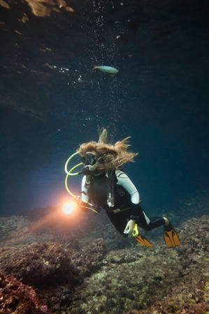 cave exploring: Scuba diver exploring underwater cave. High density of natural particles present in the water, especially visible in front of torch. Stock Photo