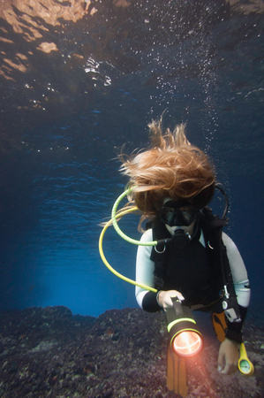 wide  wet: Young woman with long blonde hair scuba diving in the cave. Convenient copy space