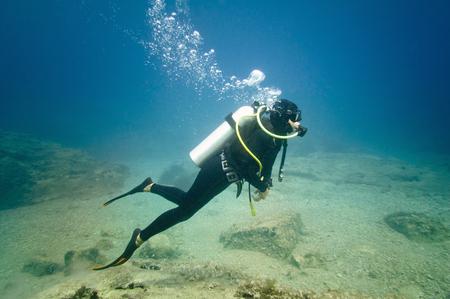 scuba diver: Young female scuba diver underwater