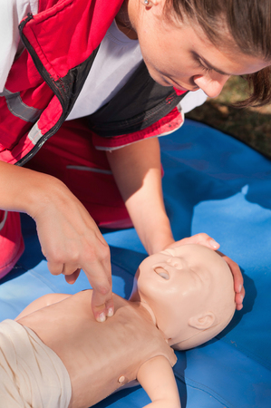 actual: Paramedic performing infant CPR. Model is team member of actual European first aid champions 20112012. Stock Photo