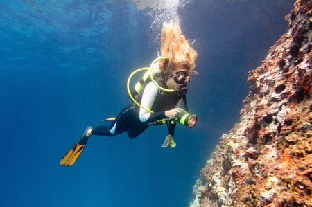 Female diver underwater with torch