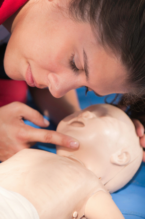 airway: CPR practitioner examining airway passages on infant dummy. Model is member of actual European first aid champions team for 20112012.