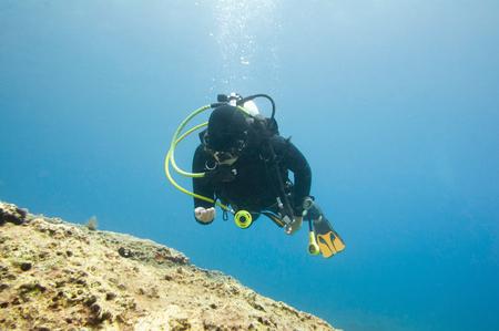 scuba diver: Scuba diver exploring the coral reef Stock Photo