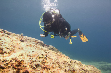 Scuba diver hovering over rocky sea floor in the Mediterranean. Polarizing filter.