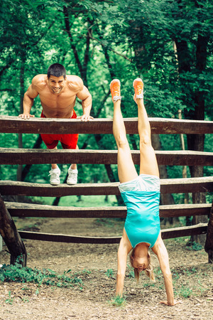 handstand: Attractive athletic couple exercising outdoors, doing push-ups and handstand at obstacle course